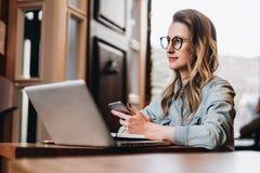 La muchacha del inconformista en vidrios de moda se sienta en café en la tabla delante del ordenador portátil, sosteniendo smartp imagen de archivo libre de regalías