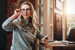 La muchacha del inconformista en vidrios se sienta en café en la tabla delante del ordenador portátil, sosteniendo smartphone Muc fotos de archivo