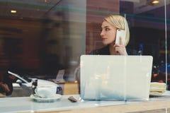 La muchacha del inconformista está llamando por teléfono vía el teléfono celular durante trabajo sobre el ordenador portátil port Imágenes de archivo libres de regalías