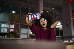 La muchacha del inconformista que usa la cámara moderna del smartphone y el wifi tienen acceso a Internet en café dentro Imagen de archivo libre de regalías