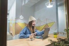 La muchacha del inconformista se sienta en un café acogedor con un ordenador portátil y sonríe Retrato de una muchacha hermosa a  fotos de archivo