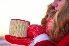 La muchacha del invierno en rojo sopla en las palmas de la nieve en el sol caliente de la puesta del sol Imagenes de archivo