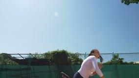 La muchacha del jugador de tenis de la mujer golpea la bola con la estafa en la cámara lenta almacen de metraje de vídeo