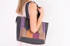 La muchacha del modelo de moda con el bolso en hombro y la parte posterior con crema del cordón se visten imagen de archivo libre de regalías