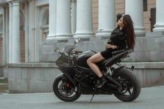 La muchacha del motorista monta una motocicleta en la lluvia opinión de la Primero-persona Imagen de archivo