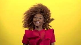 La muchacha del mulato hace las moscas el pelo Fondo amarillo Cámara lenta almacen de metraje de vídeo