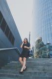 La muchacha del negocio en negro camina abajo de las escaleras que habla en el teléfono Fotos de archivo