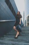 La muchacha del negocio en negro camina abajo de las escaleras que sostienen un bolso Imagen de archivo libre de regalías