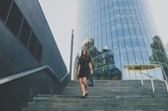 La muchacha del negocio en un vestido camina abajo de las escaleras que sostienen un bolso Fotografía de archivo libre de regalías