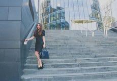 La muchacha del negocio en un vestido negro camina abajo de las escaleras Fotos de archivo