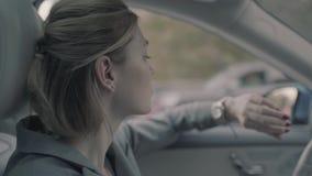 La muchacha del negocio está conduciendo un coche costoso almacen de metraje de vídeo