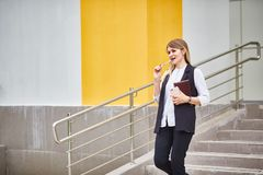 La muchacha del negocio se coloca en los pasos del edificio y piensa fotografía de archivo libre de regalías
