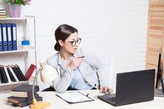 La muchacha del negocio se sienta en un ordenador en las carpetas del papel de la oficina foto de archivo