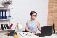 La muchacha del negocio se sienta en una oficina detrás de un escritorio con un ordenador Imagen de archivo