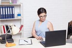 La muchacha del negocio se sienta en una oficina detrás de un escritorio con un ordenador Imagen de archivo libre de regalías