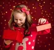 La muchacha del niño abre el regalo de Navidad en rojo oscuro con las luces imagen de archivo libre de regalías