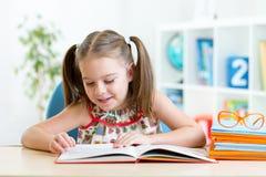 La muchacha del niño aprende leer el libro foto de archivo libre de regalías