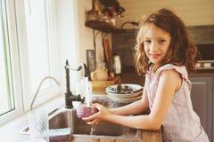 La muchacha del niño ayuda a la madre en casa y a platos del lavado en cocina Forma de vida casual en interior real foto de archivo