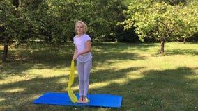 la muchacha del niño de la Escuela-edad en ropa ligera toma ejercicio del deporte en una estera en el parque Al aire libre entren almacen de metraje de vídeo