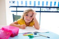 La muchacha del niño del estudiante del niño agujereó con la preparación en el escritorio imágenes de archivo libres de regalías