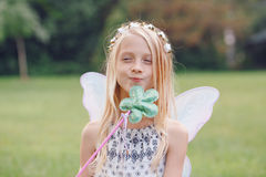 La muchacha del niño del niño con el pelo largo que lleva las alas de hadas rosadas y el tutú Tulle bordean sostener la vara mági Fotos de archivo