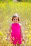 La muchacha del niño del niño en campo de flores del amarillo de la primavera y el rosa se visten Imagenes de archivo
