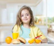 La muchacha del niño del niño que come en la tabla da fruto dentro imagen de archivo
