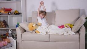 La muchacha del niño despierta de sueño Una muchacha agradable del niño disfruta de mañana soleada Buena mañana en casa metrajes