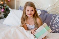 La muchacha del niño despierta en su cama por mañana de la Navidad Foto de archivo libre de regalías