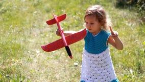 La muchacha del niño en el parque está jugando con un aeroplano El bebé enciende el avión metrajes