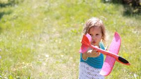 La muchacha del niño en el parque está jugando con un aeroplano El bebé enciende el avión almacen de metraje de vídeo