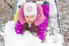 La muchacha del niño en niños resbala en el día de invierno nevoso Fotografía de archivo