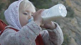La muchacha del niño en sudadera con capucha y chaleco hecho punto rojo bebe la bebida de la leche o de la lechería de la botella almacen de metraje de vídeo