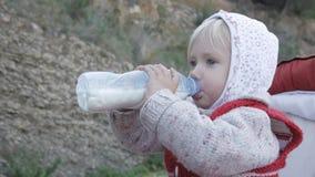 La muchacha del niño en sudadera con capucha y chaleco hecho punto rojo bebe la bebida de la leche o de la lechería de la botella almacen de video