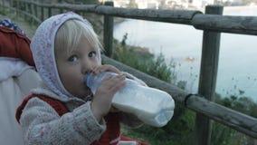 La muchacha del niño en sudadera con capucha y chaleco hecho punto rojo bebe la bebida de la leche o de la lechería de la botella metrajes