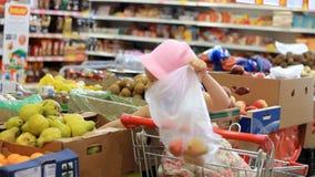 La muchacha del niño en la tienda elige la fruta Supermercado del ultramarinos y carretilla de las compras almacen de video