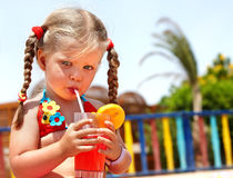 La muchacha del niño en vidrios y el bikiní rojo beben el jugo. Fotografía de archivo