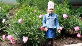 La muchacha del niño envía besos del aire Jardín con las peonías y el bebé divertido almacen de metraje de vídeo