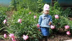 La muchacha del niño envía besos del aire Jardín con las peonías y el bebé divertido almacen de video