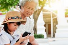 La muchacha del niño es adictiva, tiene una abuela mayor sentarse imagen de archivo libre de regalías