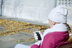 La muchacha del niño escucha la música a través de los auriculares mientras que se sienta en un banco Fotos de archivo