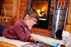 La muchacha del niño está leyendo delante de la chimenea foto de archivo libre de regalías