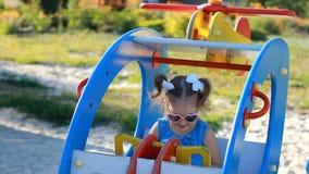 La muchacha del niño está montando un helicóptero del carrusel en un parque de atracciones Juegos del bebé en el patio almacen de video