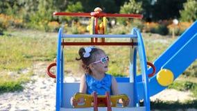 La muchacha del niño está montando un helicóptero del carrusel en un parque de atracciones Juegos del bebé en el patio almacen de metraje de vídeo