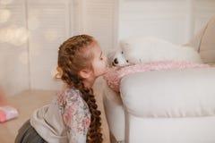 La muchacha del niño está sosteniendo el perrito en sus manos cerca de rosa las cajas de regalo fotos de archivo libres de regalías