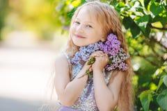 La muchacha del niño hermoso con el ramo de lila florece Fotografía de archivo