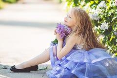 La muchacha del niño hermoso con el ramo de lila florece Imagenes de archivo