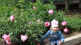 La muchacha del niño huele el aroma de la flor de la peonía y estornuda Alergias del ` s de los niños metrajes
