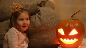 La muchacha del niño juega con las calabazas en Halloween metrajes