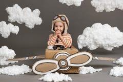 La muchacha del niño juega en un aeroplano hecho de la caja de cartón y de sueños de hacer piloto, nubes de la algodón en un back fotos de archivo